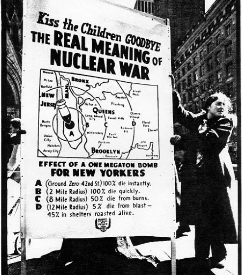 A photo of Elissa Malcon standing in front of a large poster explaining the impact of a nuclear bomb blast on New York City.